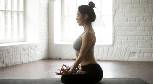 Young attractive woman sitting in Lotus pose, white loft studio