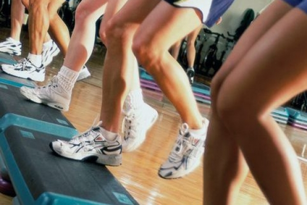 Side profile of five people doing step aerobics in a gym